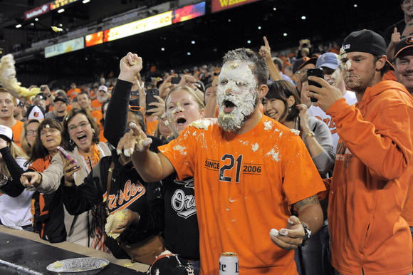 Fan Johnny Jackson of Elkridge reacts after being hit with a pie by Baltimore Orioles center fielder Adam Jones after defeating the Toronto Blue Jays Tuesday, Sep 16, 2014, as Baltimore wins its first AL East championship pennant at home since 1969. (Karl Merton Ferron, Baltimore Sun / September 16, 2014)